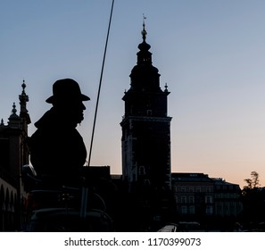 Beautiful silhouette of horse-drawn carriage coachman with in the background the old town of Krakow, Poland and the main market square