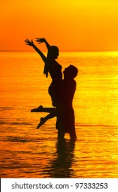 Beautiful silhouette of male holding young girl against sea sunset.