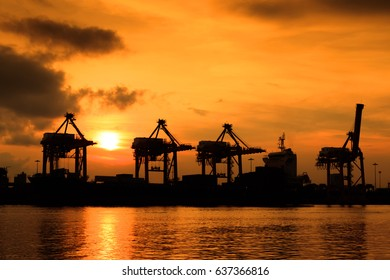 beautiful silhouette sunset of Containers Cargo port freight ship with working crane bridge in port for Logistic Import Export background, Containers loading by crane with sunrise.