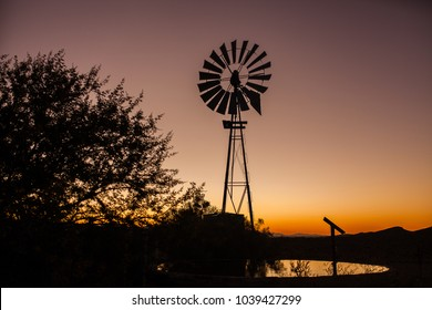 Beautiful silhouette of a windpump and a solar panel in the Klein Karoo South Africa