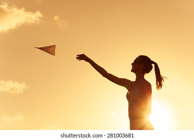 Beautiful silhouette of young woman throwing paper airplane.