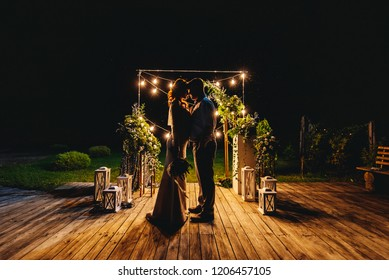 Beautiful silhouettes of the bride and groom at night on the background of bright lanterns and decor