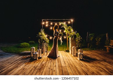 Beautiful silhouettes of the bride at night on the background of bright lanterns and decor