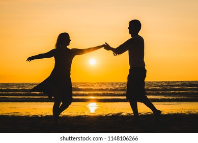 Beautiful silhouettes of two lovers dancers at sunset on a romantic beach with the sea in the background. Latin dances