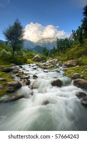 A beautiful silky running river and Himalayan mountain background in the natural surroundings of the Aru Valley of Kashmir, northern India in vertical landscape.  Copy space