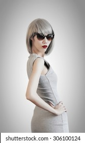 Beautiful silver hair woman, wearing sunglasses and grey dress, isolated on grey and white background