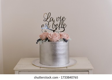 Beautiful silver metallic cake with whipped cream roses on top.