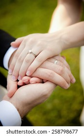 Beautiful, simple picture showing a brand new couple holding hands with gorgeous wedding rings.