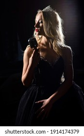 A beautiful singer in a crown performs a song on scene in a microphone. Dark silhouette on stage