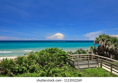 Beautiful Singer Island, Florida near Palm Beach, with a calm Atlantic Ocean, shades of blue and a striking cloud formation.  Paradise in South Florida.