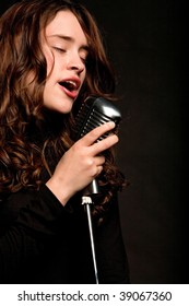Beautiful singer singing with a retro microphone