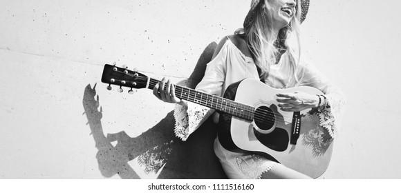 Beautiful singer songwriter playing a guitar