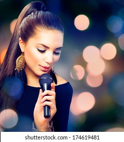 Beautiful Singing Girl. Beauty Woman with Microphone over Blinking bokeh night background. Glamour Model Singer. Karaoke song