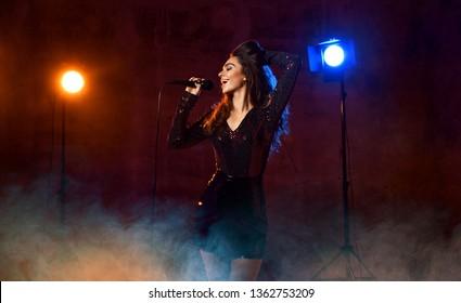 Beautiful singing girl curly afro hair singer sing with microphone karaoke song on stage on dark neon light background