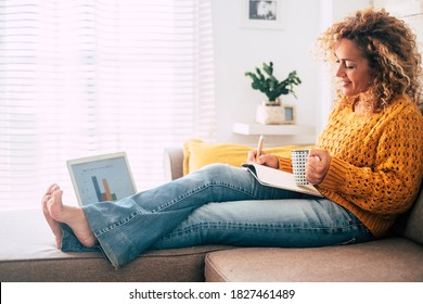 Beautiful single woman work at home with paper book and computer laptop together in old and modern job style concept - people in smat working sitting on the sofa and not in traditional office