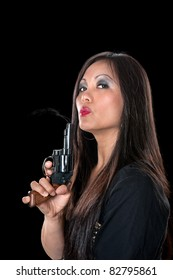 A beautiful, sinister Asian woman holding a pistol and blowing on the smoke coming out of the barrel.