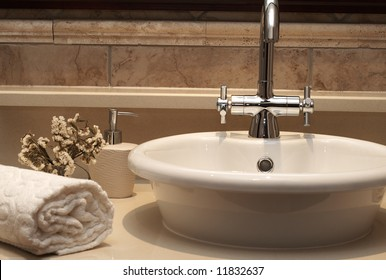 Beautiful sink in a bathroom with rolled up towel next to it and flowers