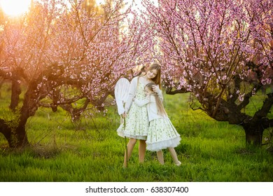 Beautiful sisters in amazing dresses in the gardens