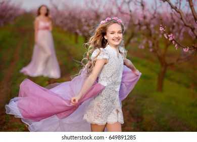 Beautiful sisters in amazing dresses, playing in the spring garden