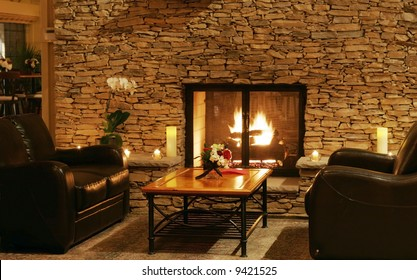 beautiful sitting area with leather couches by fire