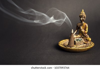 Beautiful sitting Buddha incence holder with burning cone. Meditation and yoga atmosphere