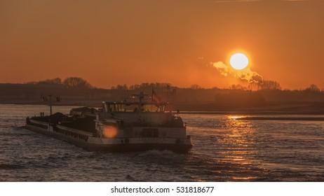 Beautiful siunrise on a foggy morning alongside the waal river by Ewijk Nijmegen with inland ship passing true Netherlands December 2016,binnenvaart Sunrise inland shipping,