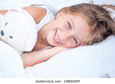 beautiful six year old girl lying in white bed with her teddy bear