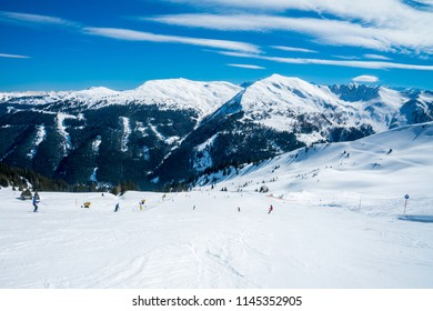 Beautiful ski resort right in the middle of the mountains in Austrian Alps. Amazing winter mountain view with small wooden houses and mountain slopes.