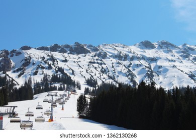 Beautiful skiing day in the Alps mountains on a sunny day in spring, chairlift out of the focus on the left side, ski piste, Oberjoch, Allgäu, Bavaria