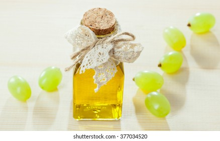 Beautiful skincare and haircare composition: bottle of natural grapeseed oil and green fresh grapes on wooden table