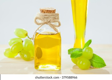 Beautiful skincare and haircare composition: bottles of natural grapeseed oil, green fresh grapes and mint leaves on wooden table