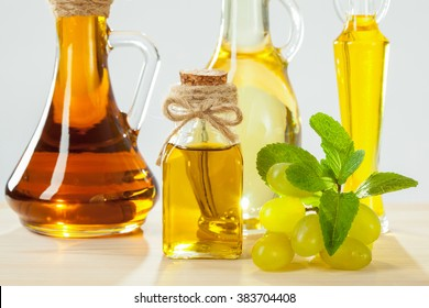 Beautiful skincare and haircare composition: bottles of natural oils, grapes and mint leaves on wooden table