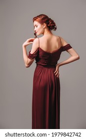 Beautiful skinny ginger girl in a burgundy evening gown. Maroon red dress with off the shoulder sleeves. Studio portrait of young lady on grey background.