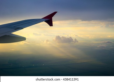 Beautiful Sky Aerial View Looking through window airplane during flight at wing with a Dramatic Golden sky sunset and Ray of Light through the cloud background