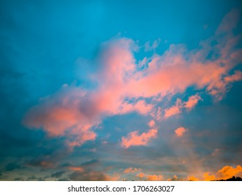 Beautiful sky background at sunset with pink, yellow, purple clouds on blue sky. Easy for text writing with copy space