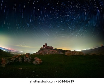 beautiful sky at night with startrails and silhouette of old Enisala fortress, Dobrogea, Romania
