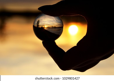 Beautiful sky on sunset over a frozen lake and its reflection in a glass ball with a silhouette of a holding hand