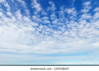 Beautiful sky over the sea with cirrus and small cumulus clouds. Background image