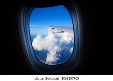 Beautiful Sky and rainbow clouds seen through window of airplane