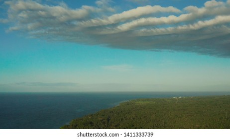 Beautiful skyscape with white clouds over the coast of the island and the blue sea, aerial view. Seascape: Ocean and sky.Philippines, Camiguin.