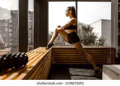 Beautiful slander girl dressed in black sports top and shorts is doing stretching on a wooden window sill in the gym