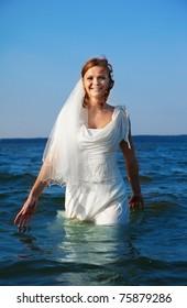 beautiful slavonic bride walking in sea waves