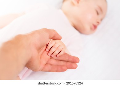 Beautiful sleeping baby with mom hand on white background