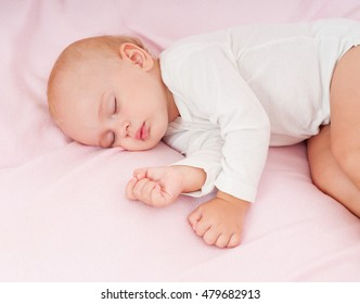 Beautiful sleeping baby. Peaceful baby lying on a bed in a bright room.