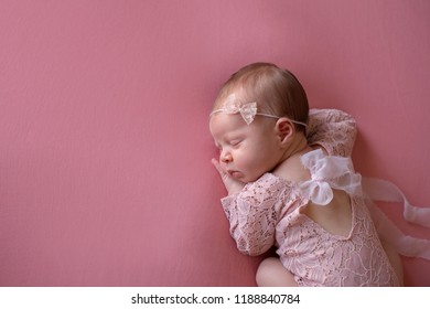 A beautiful, sleeping, newborn baby girl wearing a pink, lace romper and lace headband. Shot in the studio with a pink backdrop.