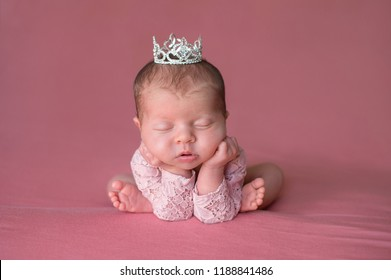 A beautiful, sleeping, newborn baby girl wearing a rhinestone tiara. Shot in the studio with a pink backdrop.