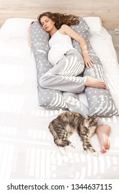 Beautiful sleeping pregnant woman with a big tummy lying in an anatomical comfortable ergonomic body pillow on the bed with the cat indoor.