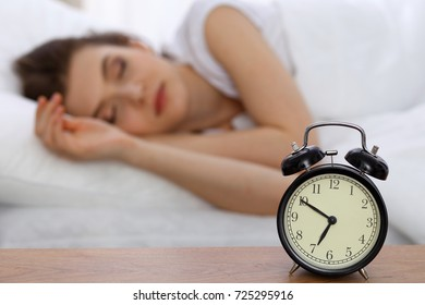 Beautiful sleeping woman resting in bed and trying to wake up with alarm clock