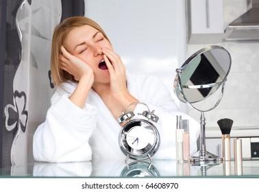 beautiful sleepy woman applying makeup at home