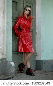 beautiful slender blonde girl in red raincoat and sunglasses
